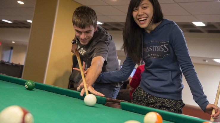 Two students playing pool in Boomer's located in the Campus Center.