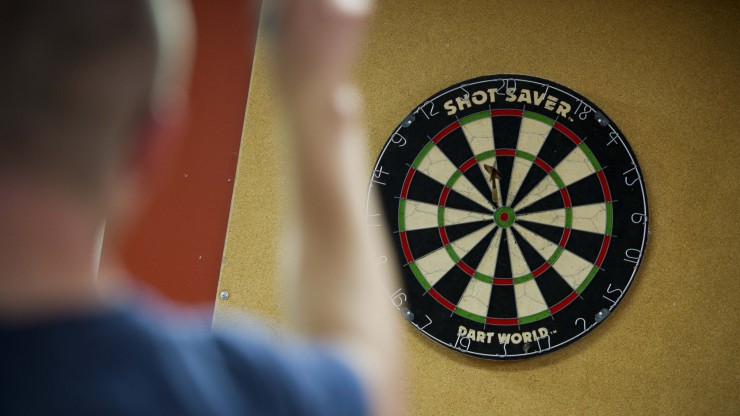 Student playing darts at Boomer's located in the Campus Center.