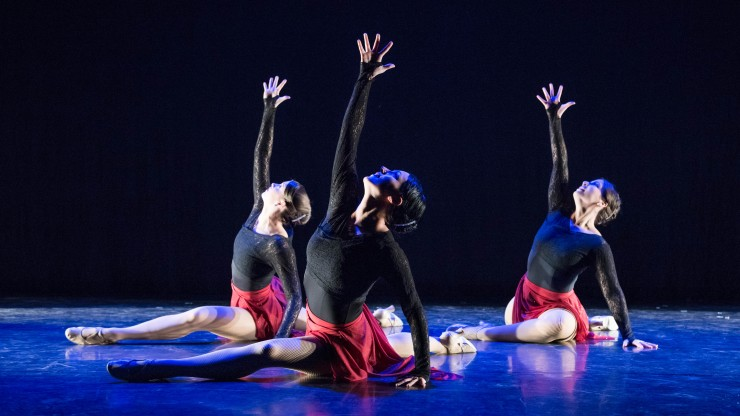 Three students on the floor onstage with their hand stretched up during a dance performance.