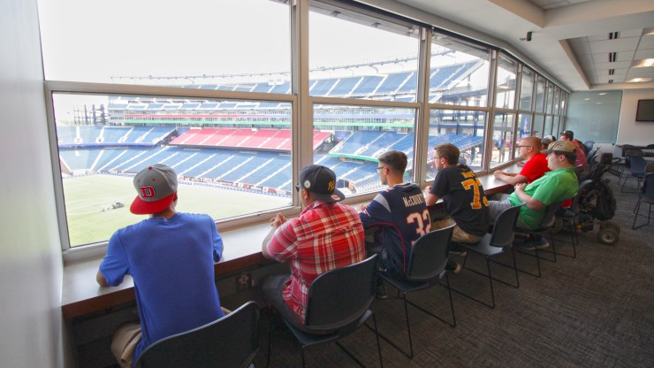 Students receiving a tour of Gillette Stadium sit overlooking the field.