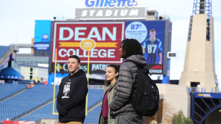 Three students on the field at Gillette Stadium.