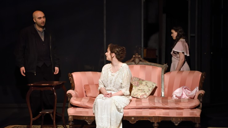 A scene from a theatre performance. Two actors speaking to each other, one is standing and the other is sitting on a couch.