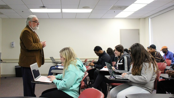 A professor gives his lecture to a group of students while they are taking notes in a Dean College classroom.