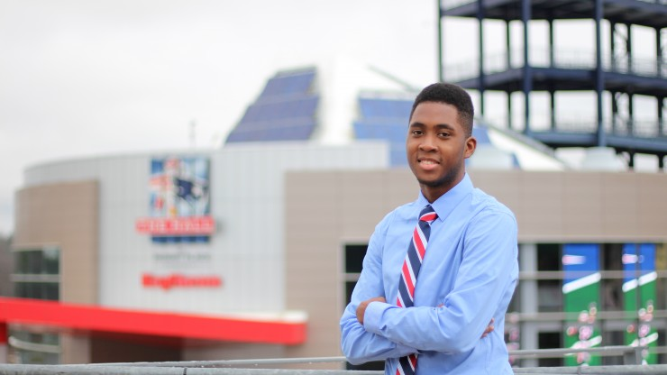 A student stands proudly smiling in front of Gillette Stadium.