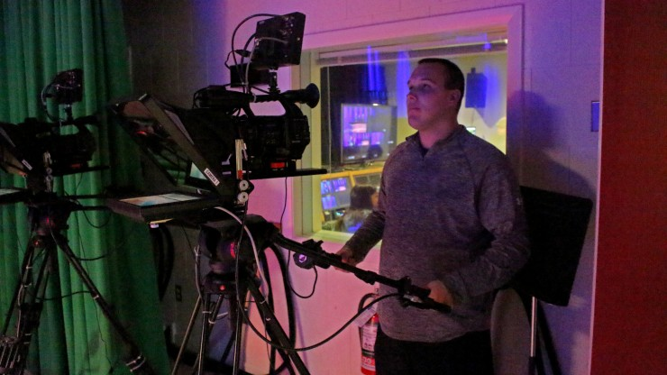 A student working the camera behind the scenes on set of Dean Today, a college news show.