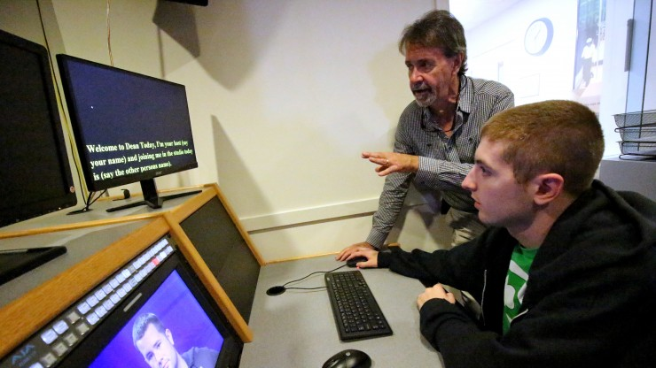 Professor helping a student in the production control room on the set of Dean Today, a college news show.