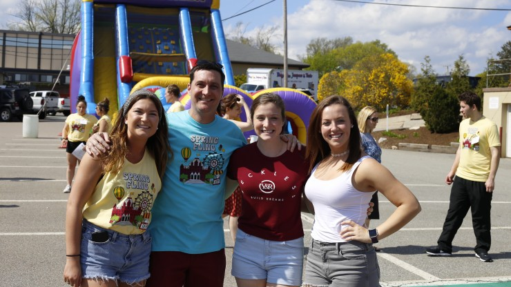 Group of students and staff at the Spring Fling carnival event outside of Dean Hall.